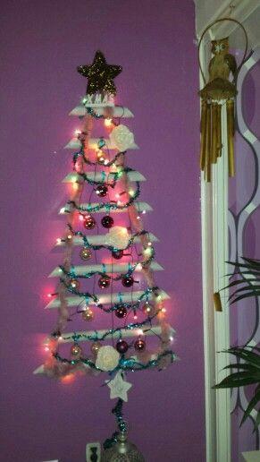 Zelfgemaakte kerstboom tegen de muur