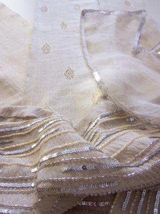 Elegant hand finished suit for cocktails and ceremonies (of Tazeen Hasan). Three pieces: ivory and gold trousers in shiny silk with small decorations; a large shawl in ivory silk profiled by silver sequins; a mini sleeveless dress with asymmetrical cut and side zipper. The beautiful overlapping veils of silk and toulle are richly embroided with beads in shades of sand, bronze and silver. It's a unique, spectacular suit.