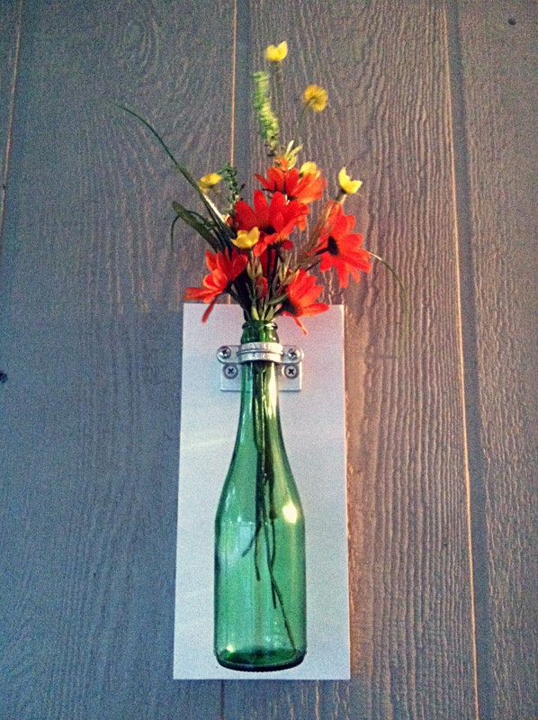"""DIY $7.00 Soda Bottle Wall Vase. I saw a blog post with this idea using a wine bottle and thought I could make it work on a smaller scale using soda bottles to decorate my porch. Here's the material list:  2x8 Wood,,3/8"""" Ceiling Flange, 3/4"""" Split Ring Hanger, 12x1x1/4 Zinc Screws, 3/8"""" Threaded Rod (cut into 3"""" pieces), What Spray Paint, Clear Acrylic Spray Paint, Soda Bottle"""