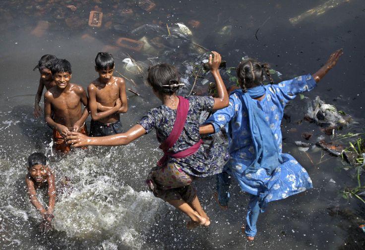 Children play in stagnant and dirty water near their shanty town in Calcutta, India, Thursday, April 1. AP / Bikas Das