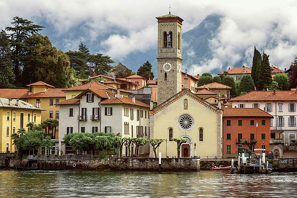 Torno On Lake Como Italy by Joan Carroll. Torno is a charming town seen from the water. The boat landing area is a small open square surrounded by the intricate beauty of the town's tightly knit dwellings, restaurants, hotels, pubs and the facade of the S