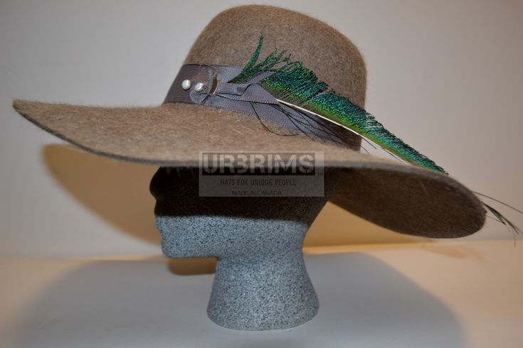 Our first Beaver fur felt style and it is the floppy hat. Stunning and natural the Rossdale beaver is a stylish, casual accessory. The beaver fur felt hat surface is defined by the mixes of color from light creamy color, light tan to medium tan coloring.  Trimmed in Carob brown, 4cm band made of Petersham ribbon. The left side (when wearing) of the hat features 2 pearlized/silver white, round buttons and silver ribbon clip. With1 stunning teal, blue and green peacock 25cm feather.URBRIMS.com