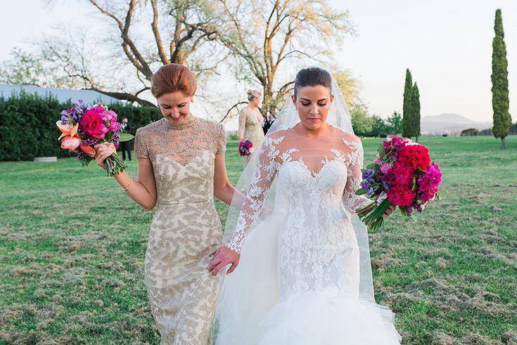 Bride and her bridesmaid walking through the vineyard.