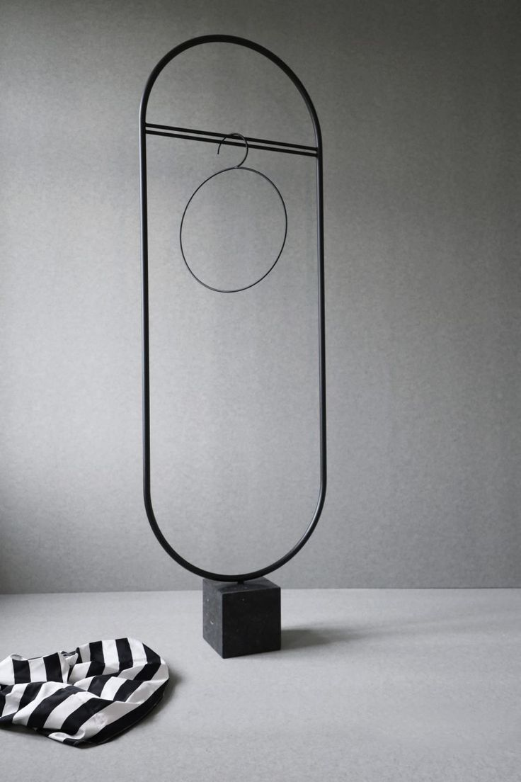 """""""Stand Out Coat Stand"""" by Linea Hildebrand. Friends & Founders.  It features a slim black frame anchored by a marble block, and comes with a set of hangers in different geometric shapes."""