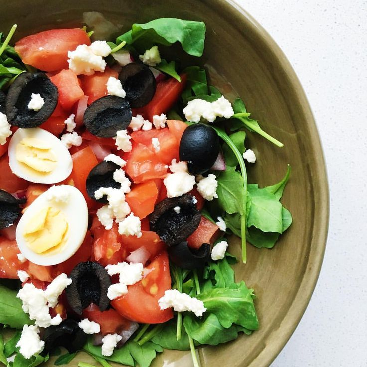Simple and easy salad with tomatoes, olives, arugula, cheese and quail eggs