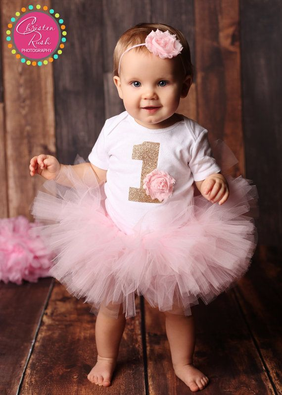 Need an outfit for your little girls first birthday or cake smash?  With this purchase you will receive:  o n e s i e >> A short sleeved onesie featuring a gold glitter number 1 with a light pink shabby chic flower. Flower is securely and professionally machine sewn on, and should never come off when tugged by little hands. All outfits are made with Carters brand onesies. Sizing chart may be found here: www.carters.com/cs-sizing.html  t u t u >> A full and fluffy light pink tutu hand knotted…