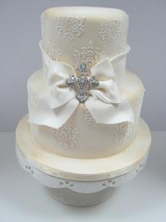 Torta de boda vintage con decoración de encaje y broche.