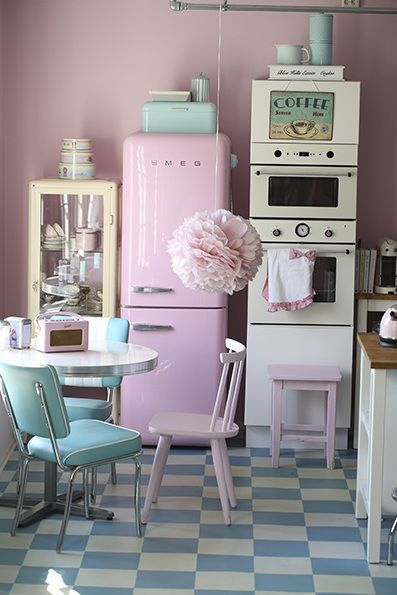 A retro-inspired kitchen.Pink wall with metallic round table and amazing pink fridge