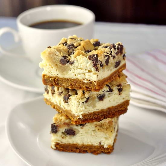 The holy grail of cookie bars!! Chocolate Chip Cookie Dough Cheesecake Bars - a perfect caloric flavor storm with a buttery graham cracker crumb crust, a vanilla cheesecake center and gobs of cookie dough on top. How's that for decadent?