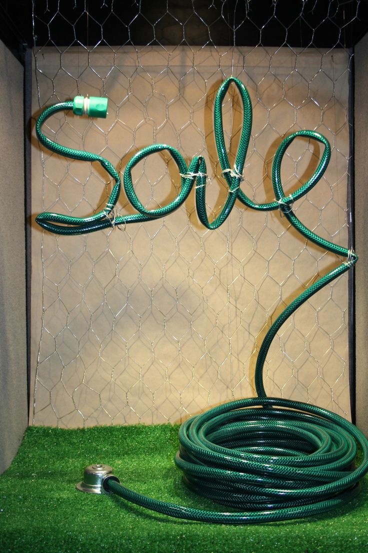 Sale window display spelled with a garden hose. Great for an end of summer sale.