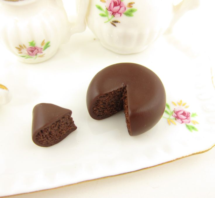 This 1-inch scale miniature polymer clay dessert is a chocolate cake with a smooth ganache glaze. It was hand sculpted out of polymer clay and has a piece cut out, showing the delicious and spongy cho