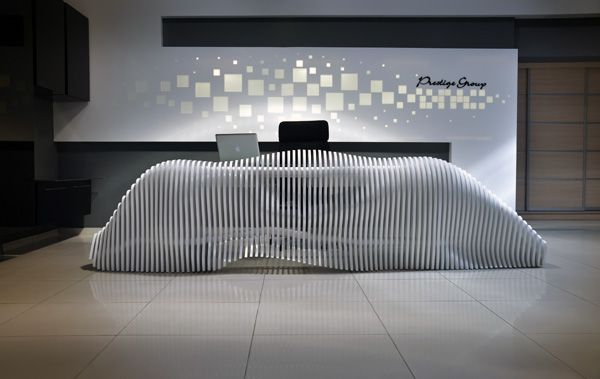 As part of a complete renovation of the showroom for the furniture brand Prestige Group in Nicosia, Cyprus- this bare, skeletal yet organic desk stands as the focal point of the updated and ultramodern reception area. Inspired by the Besparmak Mountains in North Cyprus, the sculptural desk has a rolling, cloud-like appearance that contrasts with the sharp matrix of square screens that cover the wall behind it.