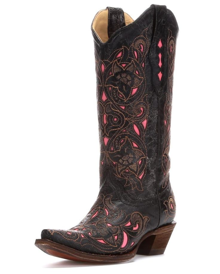 """Made with the finest exotic material, these 13"""" distressed black goat skin boots feature a floral laser cut design with pink leather inlay throughout. Tinting, abrasions, and scarring are all part of the character of the boot. Genuine leather lines the scalloped shaft, cushioned insole, and sole for comfort, while rubber gripping on the2 1/8""""heel and leather sole provides stability. Get noticed in these new vintage line boots!Corral cowgirl boots are made with western fashion details, top…"""