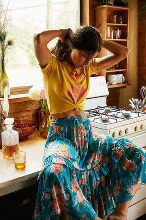 Top anudado en amarillo mostaza y falda de volante en azul estampada un outfit casual para el verano.