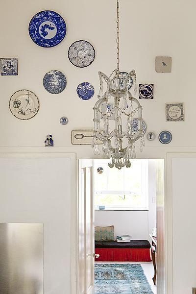 In een witte strakke keuken breng je gemakkelijk een persoonlijk accent aan door bijvoorbeeld klassieke blauw-witte bordjes boven de deuropening te hangen.