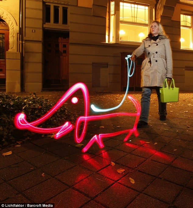 Walkies: A woman walks a sausage dog made of light down a street in Dusseldorf, Germany