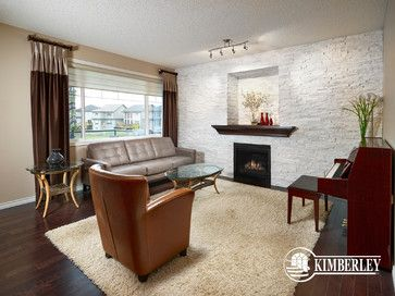 A stone wall makes for an amazing feature around this fireplace. Art niche and dark-stained mantle. Kimberley Homes, Quartz model. #interiordesign #newhomedesign #homedesign #newhome #customhome #yegre #buildwithkimberley #kimberleyhomes #fireplace #greatroom #livingroom #bonusroom #stonewall #accentwall #musicroom