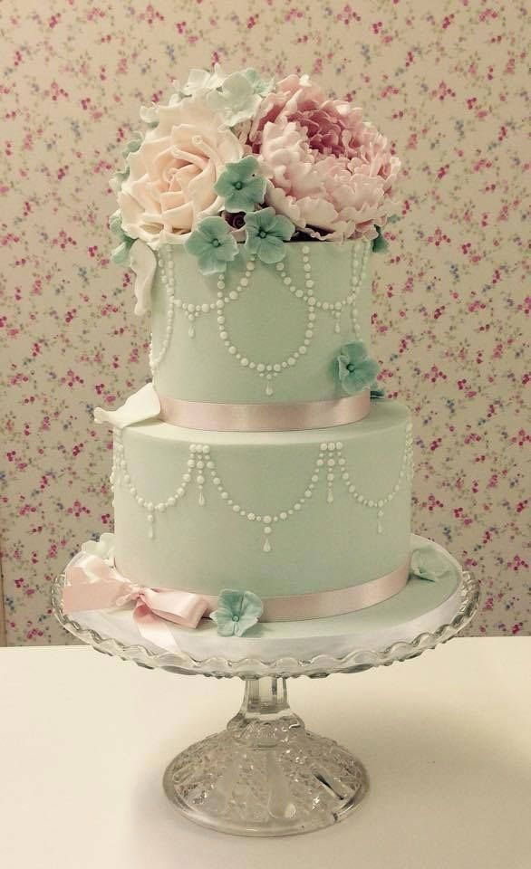 mint wedding cake with chandelier design, pink flowers and pink ribbon