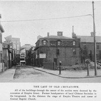 """Image of Chinatown section located in Providence, Rhode Island with a caption reading, """"The last of Old Chinatown. All of the buildings through the center of the section were doomed by the extension of Empire Street. Former headquarters of local Chinese Societies in the foreground. In the distance the stage of Empire Theatre and tower of Central Baptist Church."""""""