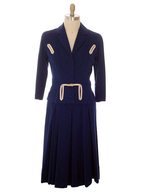 Incredible vintage 1940s Fernande Desgranges France navy wool knit ladies suit with white leather trim.  Its a gorgeous suit! The jacket is very fitted, and has French Buttonhole pockets on the breast and on the peplum, that one becoming part of the belt in front. It has light shoulder pads. 3/4 Sleeves.  The skirt is fitted at the waist with another set of leather trimmed faux buttonholes. The leather has gold colored tips. It fits at the hips and then has huge pleats for extreme fullne...