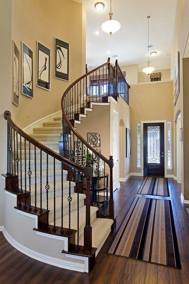 Curved staircase with wrought iron spindles.