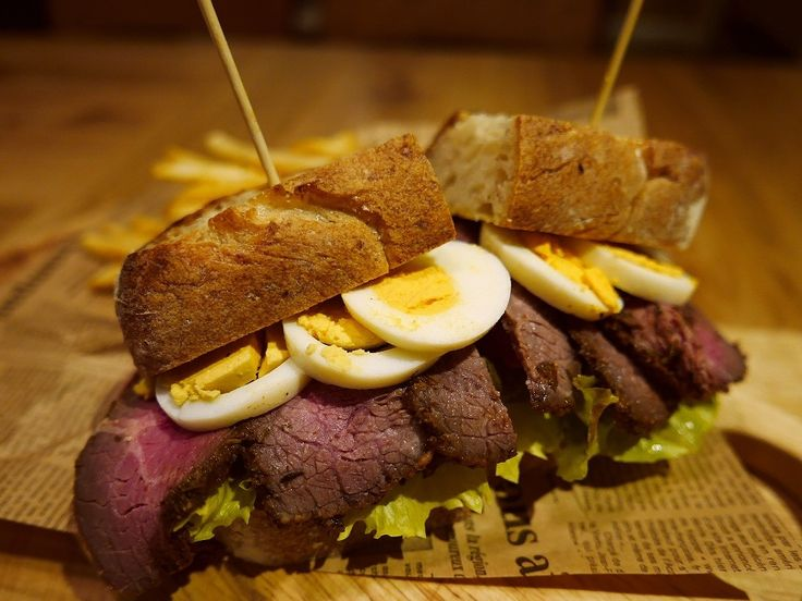 Sandwich of home made pastrami beef. hard boiled eggs, lettuce, tomato.