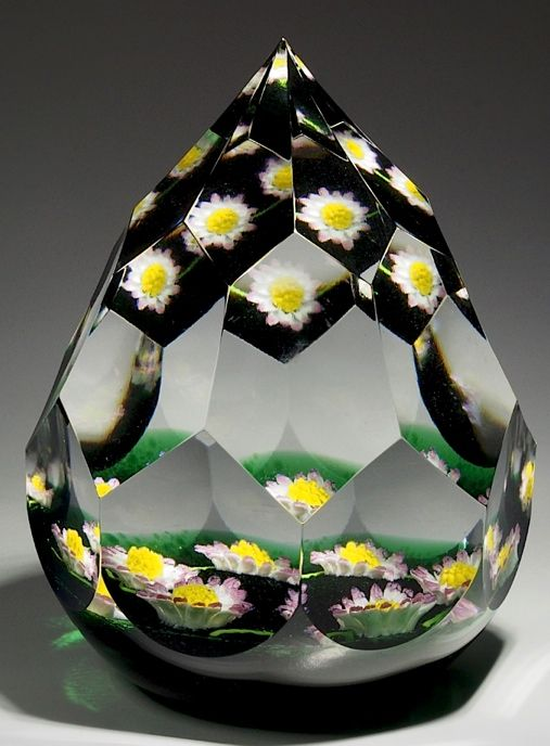 "Caithness {Scotland} paperweight -   A garland of five pink and white petaled flowers with yellow stamens is connected by a green stem. Garland rests on a translucent green ground and has a multi-faceted pyramidal shape. Signed with a ""CG"" signature cane. 3 1/8""w x 4""t, 23.3oz. - #0338"