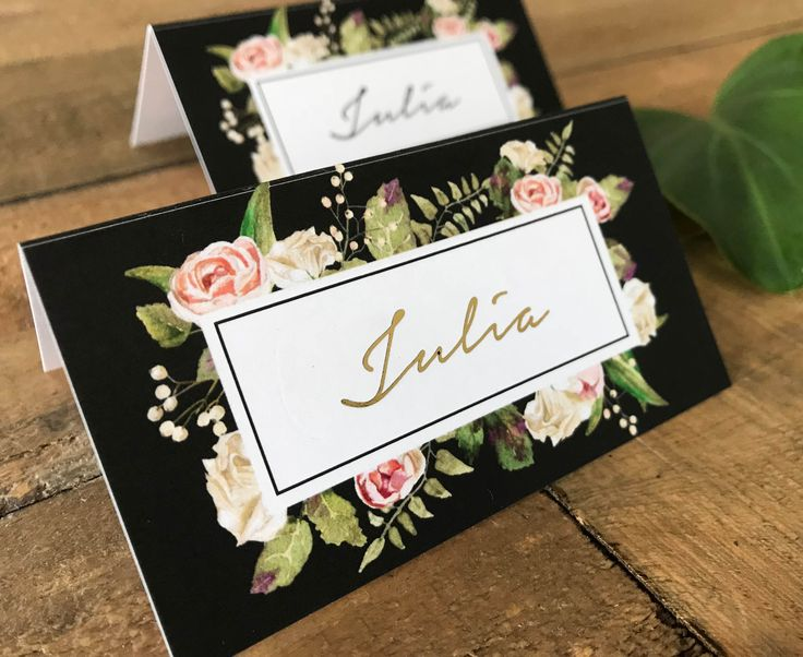 A gorgeous set of floral place cards | tent cards | escort cards featuring blush and cream/beige roses and green foliage on a charcoal background.