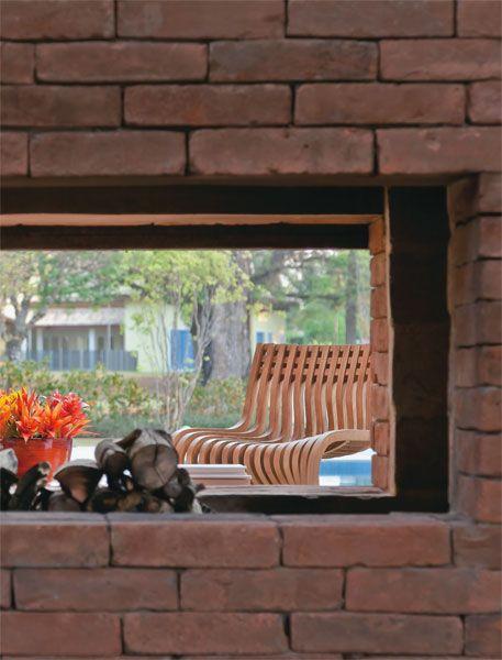 está a lareira dupla, que serve tanto ao interior quanto ao exterior. A segurança fica garantida por uma portinhola de ferro oxidado.