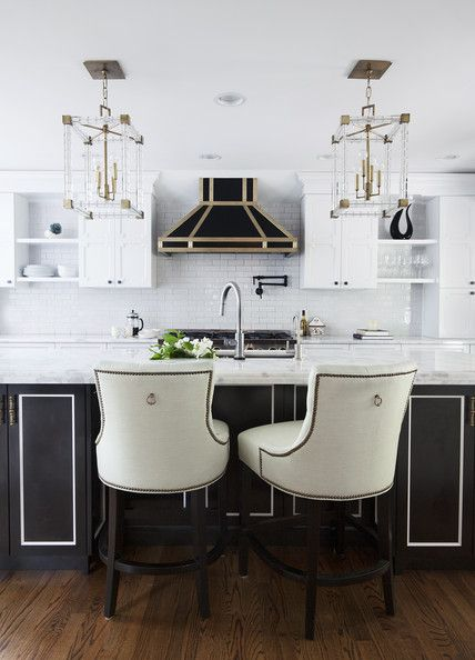 A dramatic black-and-white kitchen with lucite-and-gold light fixtures create a glamorous space.