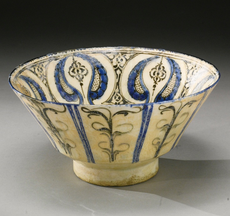 A KASHAN BOWL WITH ABSTRACT MOTIFS, PERSIA, EARLY 13TH CENTURY. of deep round form on a tall foot, the cobalt blue and black decoration featuring an abstract vegetal design, with stylised petals and leafy motifs, filled in the interstices with fine black foliate decoration, under a transparent glaze 22.9cm. diam. 10.2cm. height.