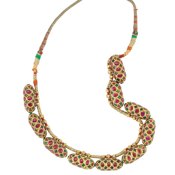 Indian Gold, Foiled-Back Ruby, Emerald and Cord Necklace The cord necklace strung with ten bullet-shaped beads set throughout with foiled-back oval rubies, spaced by diamond-shaped foiled-back emeralds, all outlined in gold, one ruby missing, approximately 75 dwt. gross. Length adjustable.