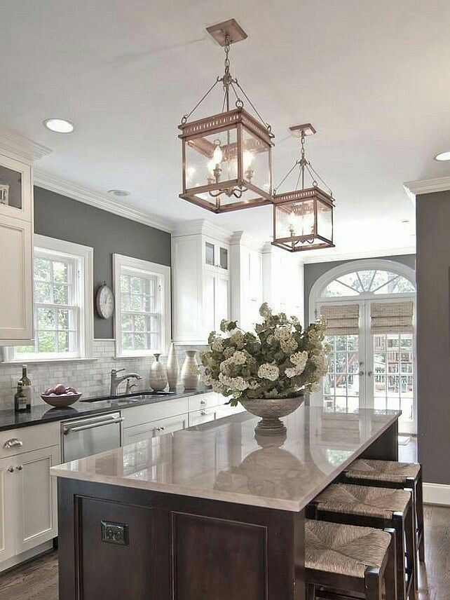 A lovely example of a neutral kitchen. The beautiful cieling lamps above the island make the whole kitchen.