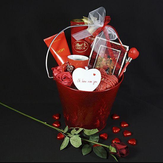 """Ik hou van jou!   Een prachtige rode emmer Een tube showergel merk: Joop Een prachtige fluwelen koker met luxe Lindt bonbons Een doosje met schattige kleine rode roosjes en een boekje """"Hartstocht"""" Een aparte moderne rode kaars in vorm Een rood kopje met zilveren decoratie hartje Een wit houten decoratiehart met de tekst """"Ik hou van jou"""" Twee heerlijke geurende zeeproosjes Een rode hart balpen Een Valentijns wenskaart"""