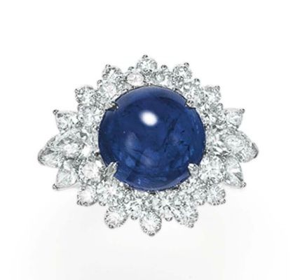 Set with a cabochon sapphire, weighing approximately 9.33 carats, within a circular and pear-shaped diamond surround, mounted in 18k white gold, with French importation mark.