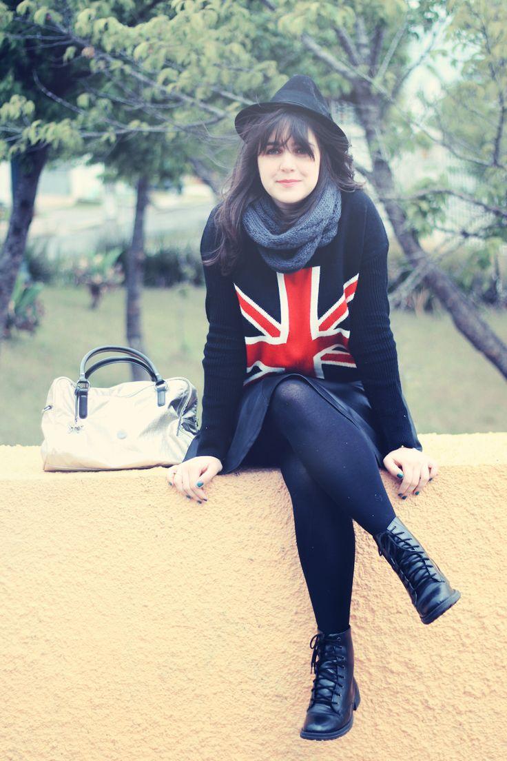 Look de inverno com saia preta rodada suéter estampado com bandeira do Reino Unido meia calça coturno chapéu e bolsa prateada da Kipling