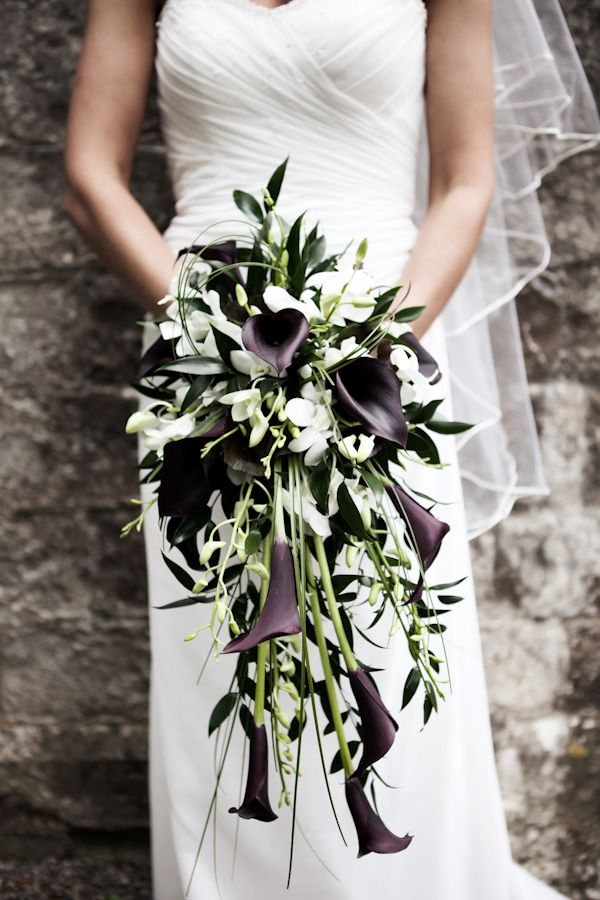 Such an elegant and modern long cascade bouquet of white dendrobium orchids, dark purple calla lilies, italian ruscus and bear grass. - Check out navarragardens.com for info on a beautiful Oregon wedding destination!