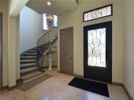 CUSTOM HOME - entry way. iron scroll door. winding staircase. lago vista lake travis austin texas hill country