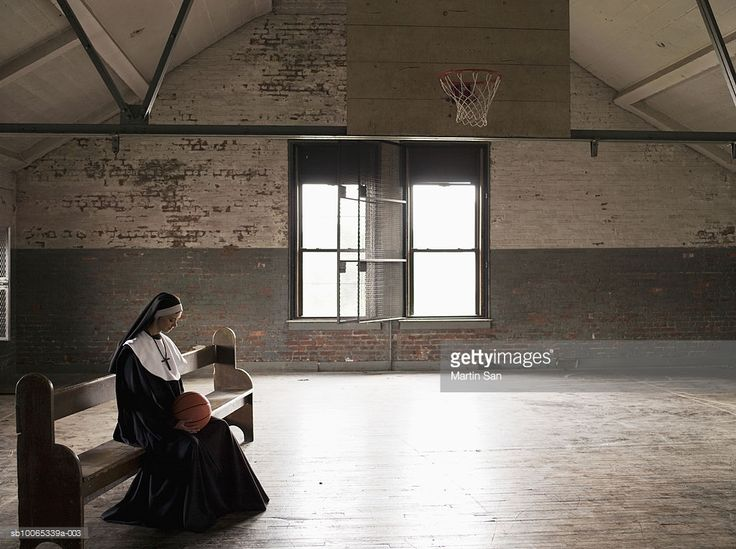Stock Photo : Young nun sitting on bench in court holding basketball