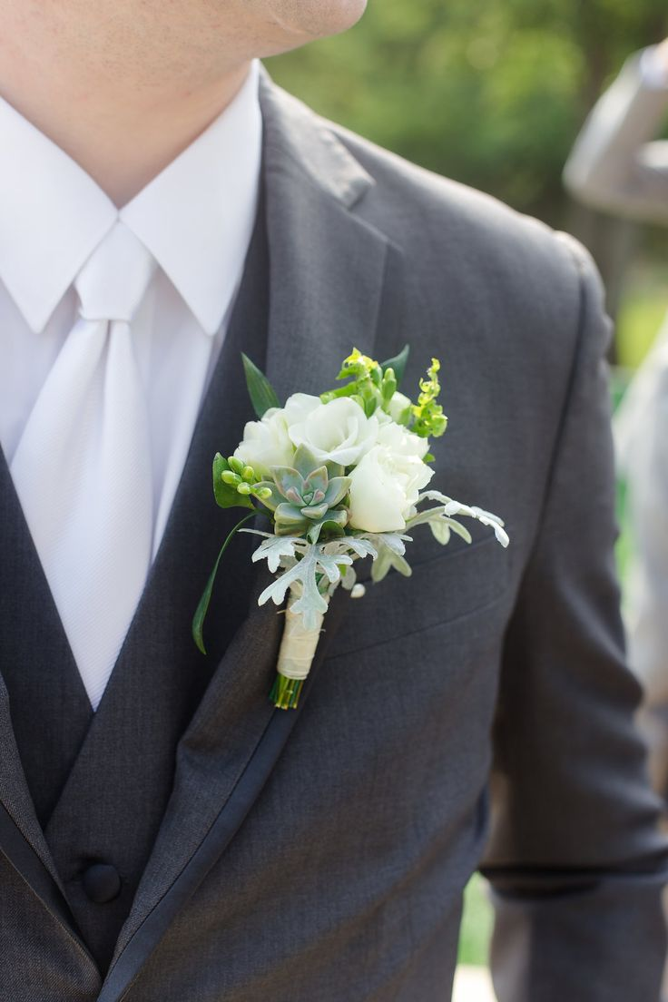 The perfect groom look for a pastel wedding--a dark gray//charcoal suit, white and mint boutonniere, and white tie. Taken at THE SPRINGS Event Venue in Aubrey, TX. Book your free tour today! Photographer: Julia M Photography