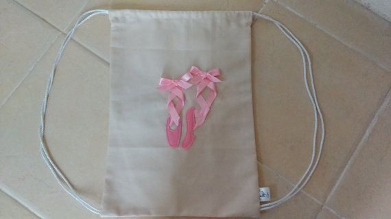 This simple gym bag will provide the perfect storage solution for all your dancers equipment. With a felt and ribbon ballet shoe detail on the front and a plain back. The canvas bag can be closed by pulling the drawstring straps on either side of the bag. The bag can be personalised with a name displayed under the shoe detail. The bag measures 41 cm x 36 cm when laid flat not including the straps. To request a personalised name on the bag please message when ordering otherwise the item will…