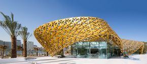 the 'Butterfly Pavilion' on Al Noor Island, Sharjah, U.A.E., designed by 3deluxe, whose ornamental roof structure gives the island its defining characteristic, houses more than 500 species in a unique biosphere. Inside the intervention's glass-box exterior, a 3D-modeled surface — made of thermoformed krion — extends seamlessly across all walls and the floor's entirety without repeating a single pattern.