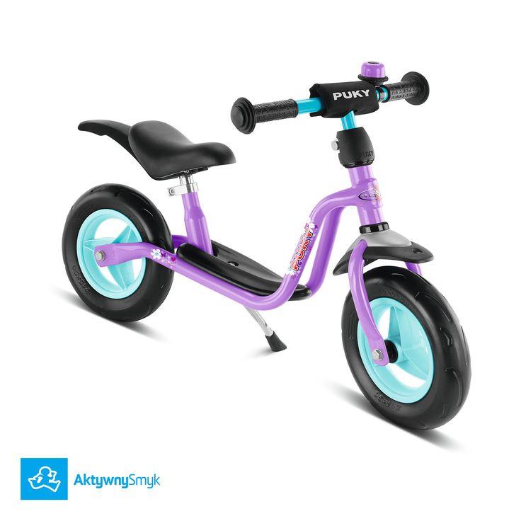 Fioletowy rowerek biegowy Puky LR M Plus dla dziecka od 85 wzrotu (średnio ponad 18 dziecko). Ten model wyposażono dodatkowo (w stosunku do Puky LR M) w błotniki, nóżkę i dzwonek.