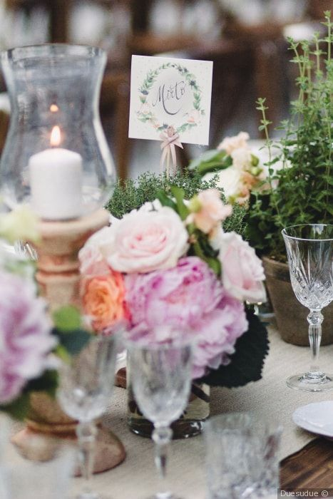 Decorazioni per la tavola del banchetto di nozze con candele e fiori freschi. Centrotavola con erbe aromatiche