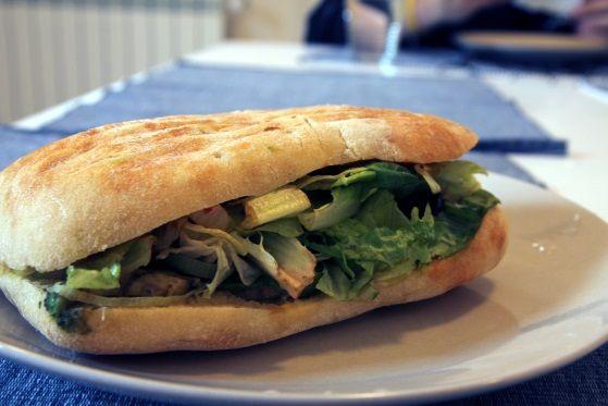 Sandwich vegan cu humus, avocado, măsline, sos de roșii și salată lollo