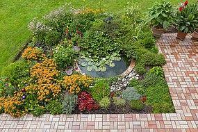 Kleiner Garten mit Teich und Terrasse.