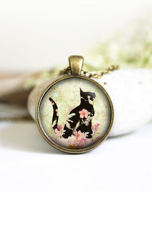 Halsband med katt och blommor   Foxboheme - Ett bildhalsband med en svart katt med blommor och grön bakgrund. Ramen finns i ljus silver, antiksilver, brons och svart och bilden är täckt med en glaskupol.