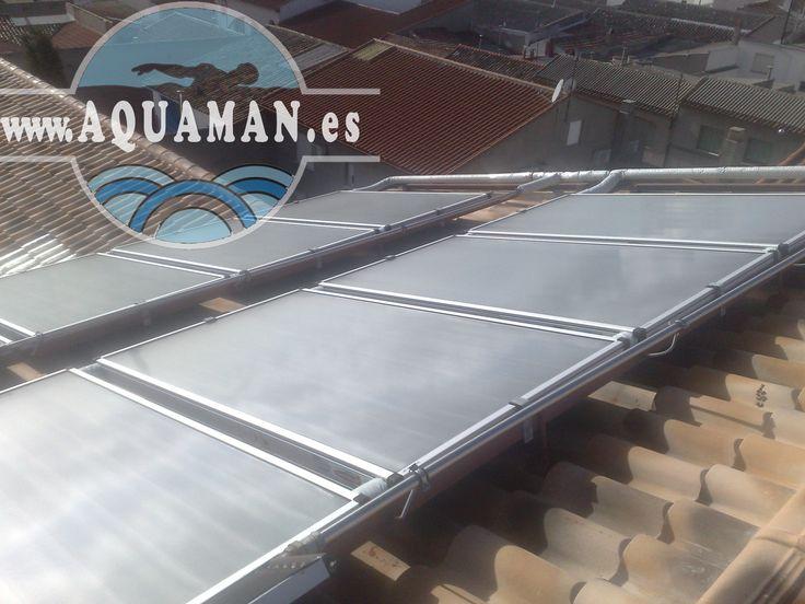 Placas solares para calentar el agua de la piscina instaladas en el tejado de la vivienda.