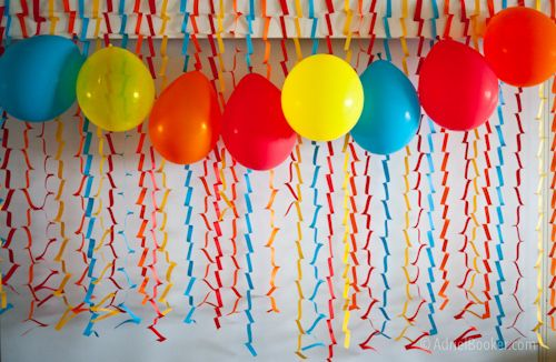 paper zig-zags and balloons strung on thread - the easiest party backdrop ever. fast to make and cute and cheap!