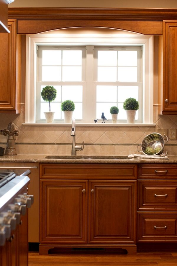 Kitchen Sink With A Window And Decorative Woodwork Above